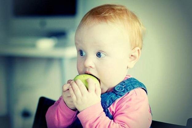малышка кушает яблоко